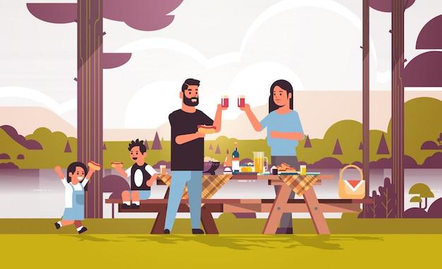 Gelukkige ouders en kinderen die hotdogs eten die sapfamilie drinken die het concept hebben van het picknickweekend van de de rivierbank landschapsachtergrond vlakke volledige horizontale lengte als achtergrond