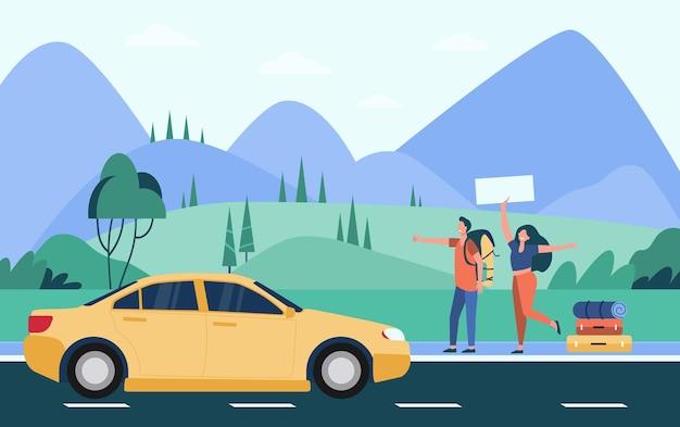 Gelukkige paar toeristen met rugzakken en kampeerspullen liften op de weg en gele auto thumbing