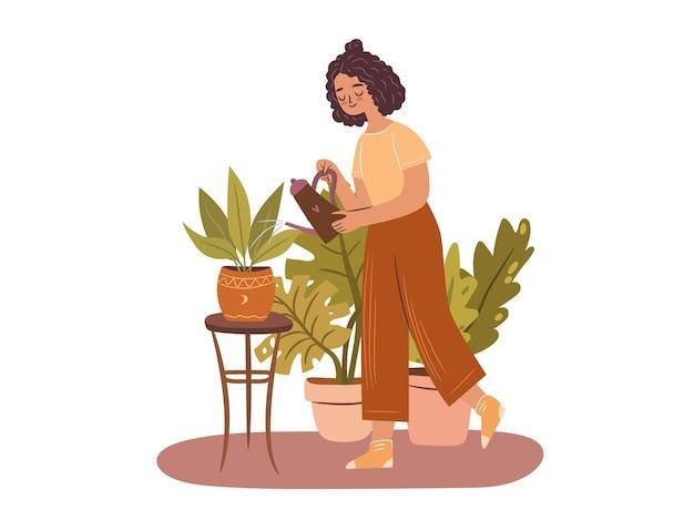 Gelukkige plant dame jonge afro-amerikaanse vrouw die een potplant water geeft op een witte achtergrond