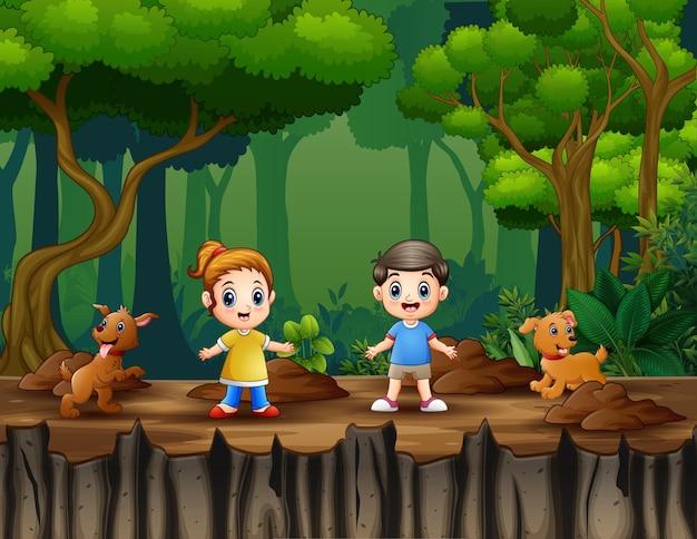 Gelukkige twee kinderen met hun huisdieren in een bos