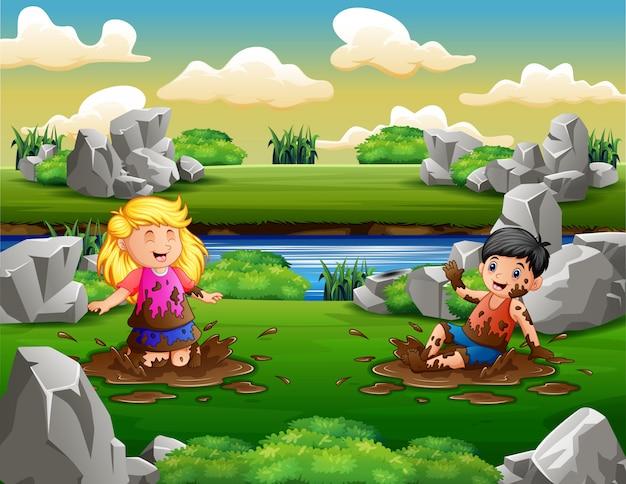 Gelukkige twee kinderen spelen in modder plas