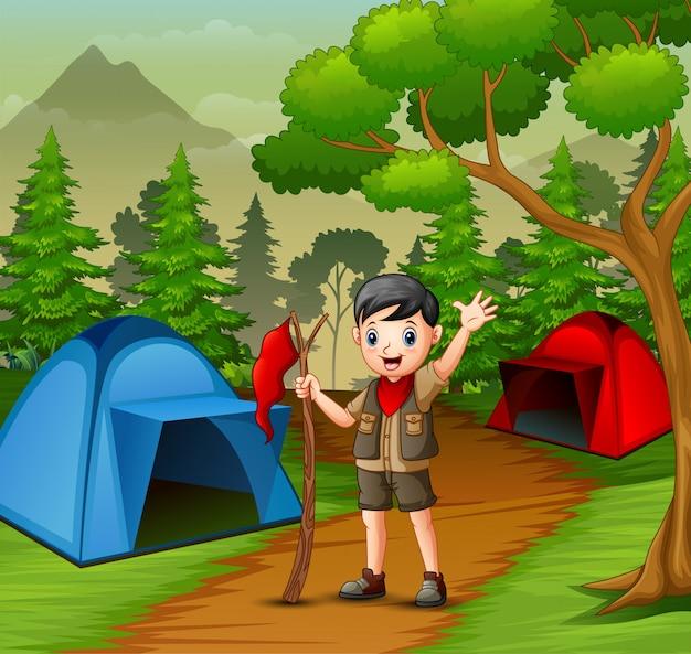 Gelukkige verkennersjongen die in bos kampeert