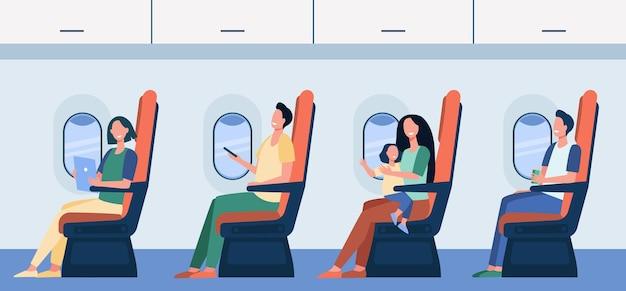 Gelukkige vliegtuigpassagiers zittend op hun stoel, gadgets gebruiken, kind op schoot houden, drinken uit stok