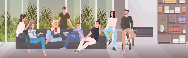 Gelukkige vrienden die tijd samen doorbrengen mannen vrouwen die op bank zitten die het binnenland van de pretwoonkamer hebben