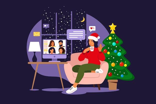 Gelukkige vrienden vieren kerstmis en nieuwjaar. thuis online feest. meisje in een kerstmuts communiceert met vrienden via een videogesprek.