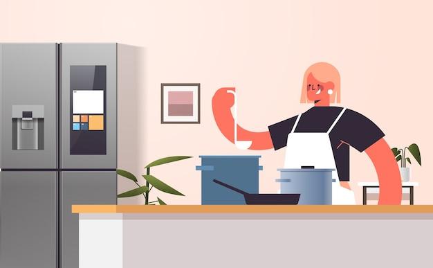 Gelukkige vrouw bereiden van voedsel in de pan koken thuis concept moderne keuken interieur horizontaal portret