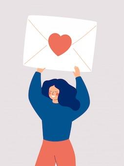 Gelukkige vrouw die een grote envelop met een rood hart boven haar hoofd houdt dat op wit wordt geïsoleerd.