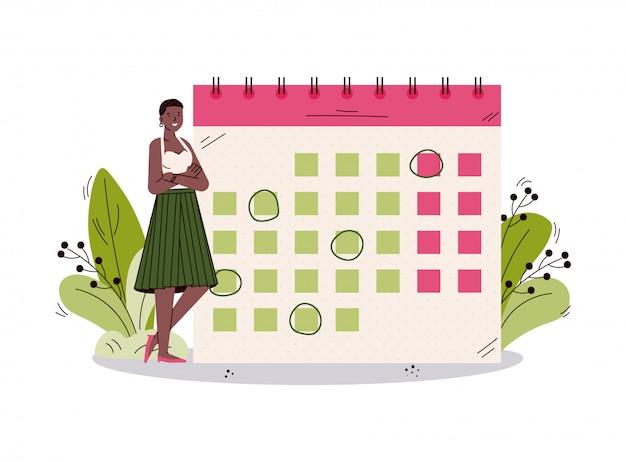 Gelukkige vrouw die kalender met het schema van de maandgebeurtenis bekijkt.