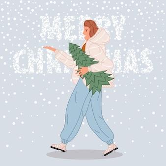 Gelukkige vrouw die met kerstboom loopt wijfje die in kerstmanhoed op sneeuwachtergrond draagt