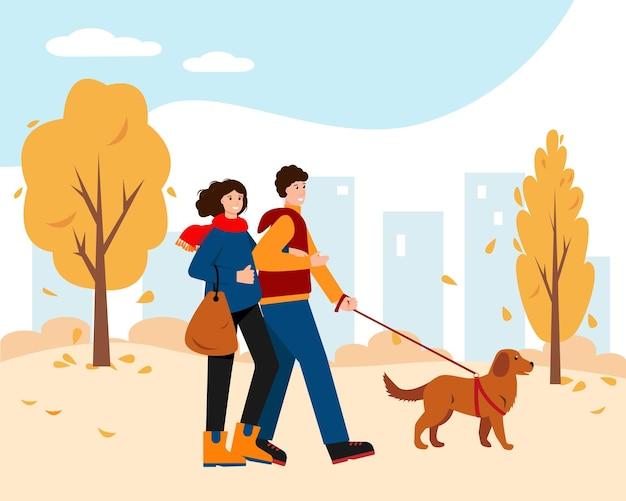 Gelukkige vrouw en man in herfst park met hond.
