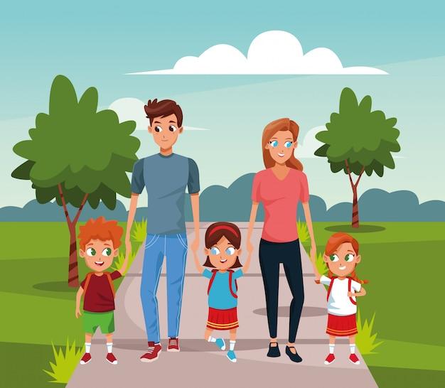 Gelukkige vrouw en man met kinderen lopen in het park