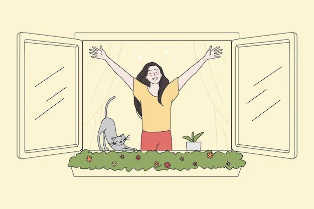 Gelukkige vrouw kijkt uit het raam en ademt frisse lucht in
