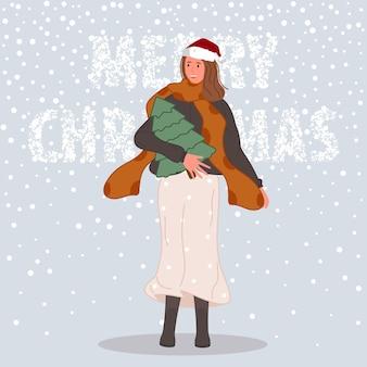 Gelukkige vrouw met kerstboom wijfje die in kerstmanhoed op sneeuw achtergrondconcept dragen