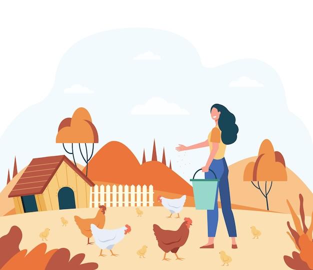 Gelukkige vrouw voederen binnenlandse vogels platte vectorillustratie. cartoon vrouwelijke boer kippen en hanen fokken op land. kippenboerderij en landbouw concept