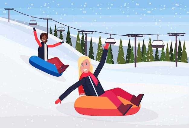 Gelukkige vrouwen die op sneeuw rubberbuis sledding in de berg