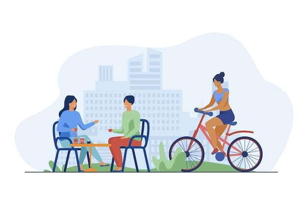 Gelukkige vrouwen zitten in straatcafé en fietser rijden in de buurt van hen. koffie, fiets, meisje platte vectorillustratie. zomer en stedelijke levensstijl