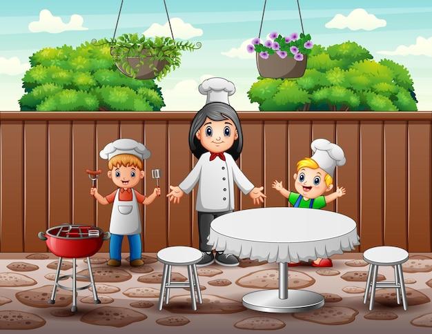 Gelukkige vrouwenchef-kok en kinderen in het restaurant