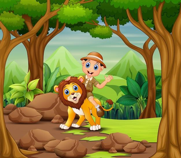 Gelukkige zookeeperjongen en leeuw in een bos