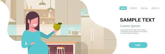 Gelukkige zwangere vrouw die groene appelzwangerschap en moederschap houdt