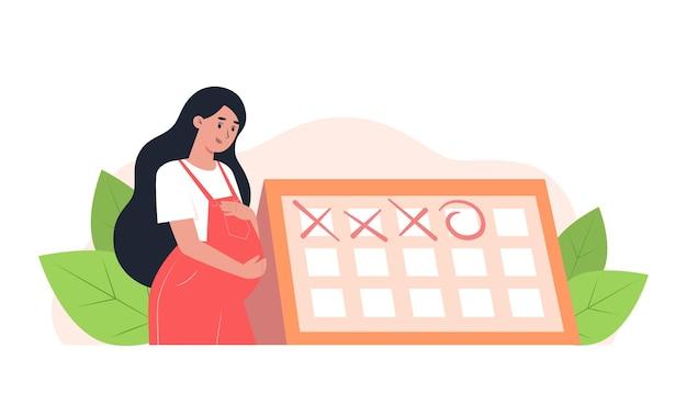 Gelukkige zwangere vrouw staat in de buurt van de kalender, geplande afspraak met een verloskundige-gynaecoloog