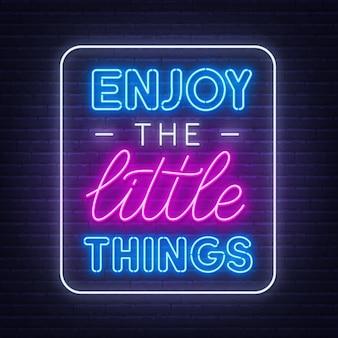 Geniet van het inspirerende citaat van kleine dingen op een bakstenen muurachtergrond.