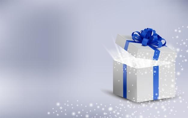 Geopende kerstdoos met gloeiende glitterglitters en magisch licht erin. witte doos in een blauw lint en een strik bovenop.