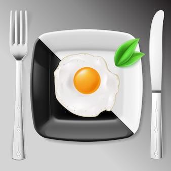 Geserveerd ontbijt. gebakken ei op zwart-wit bord geserveerd met mes en vork