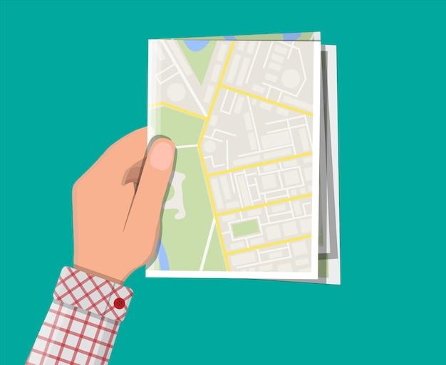 Gevouwen papieren stadsplattegrond in de hand