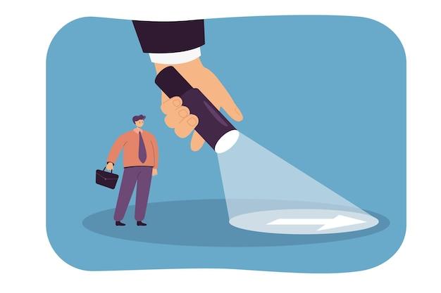 Gigantische hand schijnt zaklamp voor zakenman