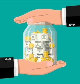 Glazen geldpot vol gouden munten en bankbiljetten en handen. dollar munt in spaarpot opslaan. groei, inkomen, sparen, investeren. symbool van rijkdom. zakelijk succes.
