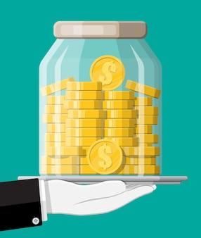 Glazen geldpot vol gouden munten op dienblad. dollar muntstuk opslaan in spaarpot. groei, inkomen, sparen, investeren. symbool van rijkdom. zakelijk succes. vlakke stijl illustratie.