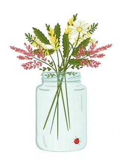 Glazen pot met boeket van wilde bloemen binnen