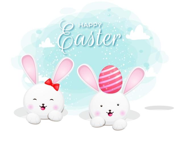 Glimlachend leuk konijntjespaar dat uit gat met ei gluurt