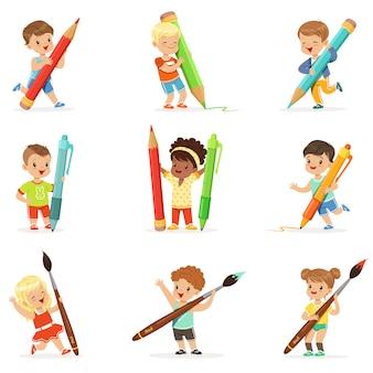 Glimlachende jonge jongens en meisjes met grote potloden, pennen en penselen, ingesteld voor. het beeldverhaal detailleerde kleurrijke illustraties