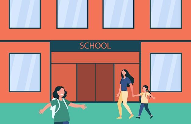 Glimlachende kinderen die met rugzakken naar school gaan.