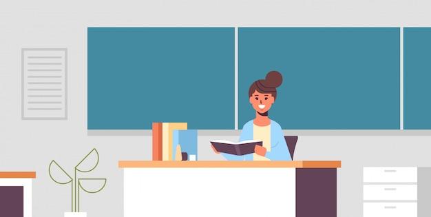 Glimlachende leraarszitting bij bureauvrouw die studentenvoorschrift voor groen schoolbordonderwijsconcept controleren modern klaslokaal binnenlands horizontaal portret