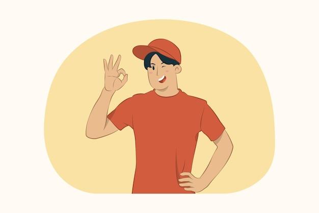 Glimlachende leveringsjonge mens die ok gebaarconcept toont