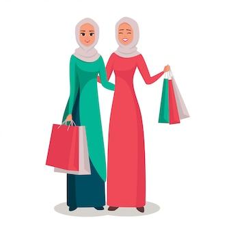 Glimlachende moslimvrouwen in hijab met het winkelen zakken
