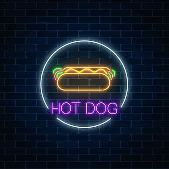 Gloeiende neon teken van hotdog in cirkelframe op een donkere bakstenen muur