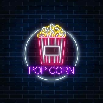 Gloeiende neon teken van pop corn in cirkelframe op een donkere bakstenen muur