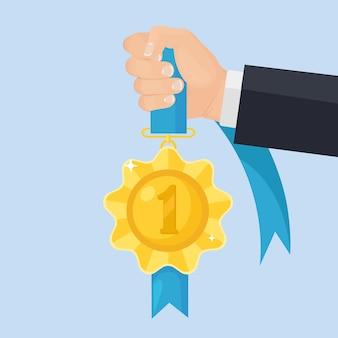 Gouden medaille met blauw lint voor de eerste plaats in de hand. trofee, winnaarsprijs op achtergrond. gouden kentekenpictogram. sport, zakelijke prestaties, overwinning.
