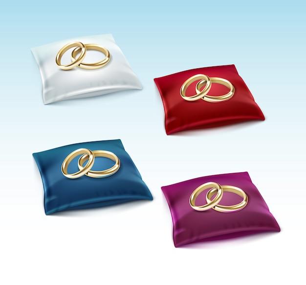 Gouden trouwringen op rood wit blauw paars satijnen kussen