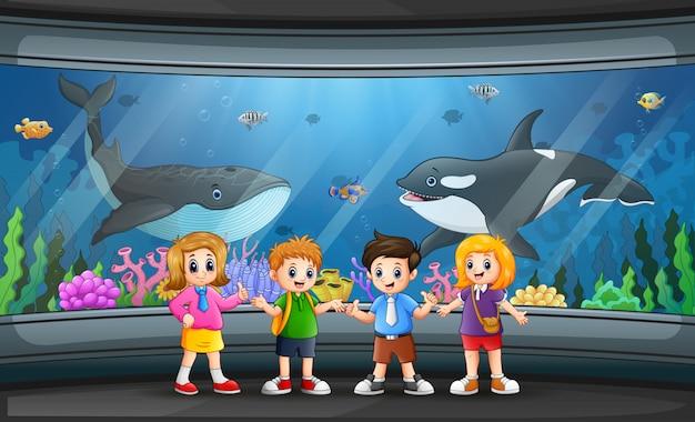 Grappige schoolkinderen die vissen in aquarium bekijken
