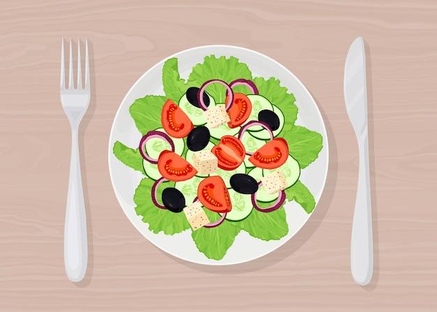 Griekse salade met feta, tomaten, olijven, groene slablaadjes bovenaanzicht. bord met vork, mes