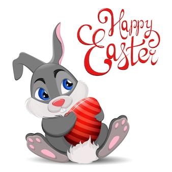 Grijs pasen-konijn die en ei zitten houden.