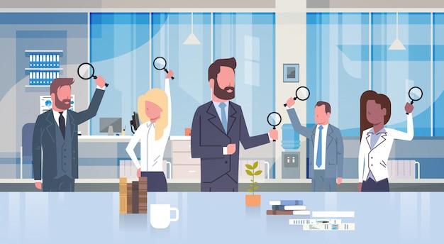 Groep bedrijfsmensen die vergrootglas houden die in modern bureauconcept werken team van businessm