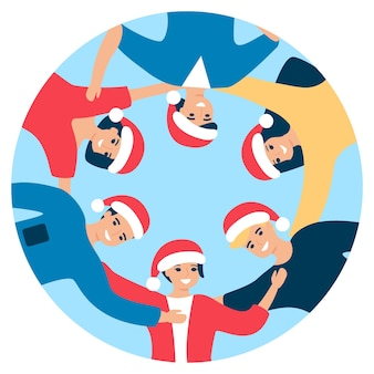 Groep gelukkige mensen in kerstmuts staan in cirkel en knuffelen.