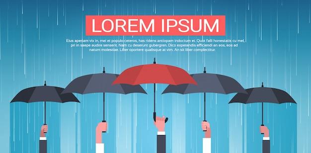 Groep handen die paraplu unger huge rain background back achteruitzichtbeschermingconcept houden