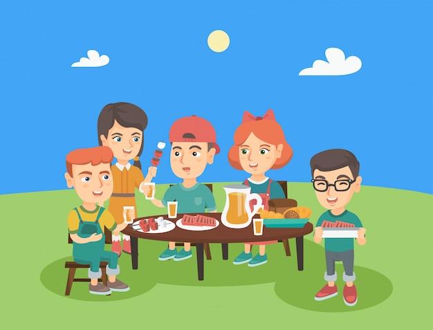 Groep kaukasische kinderen die pret hebben bij picknick.