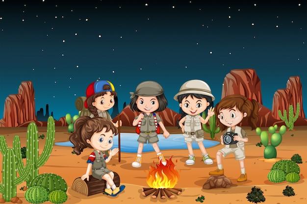 Groep kinderen die in de woestijn kamperen